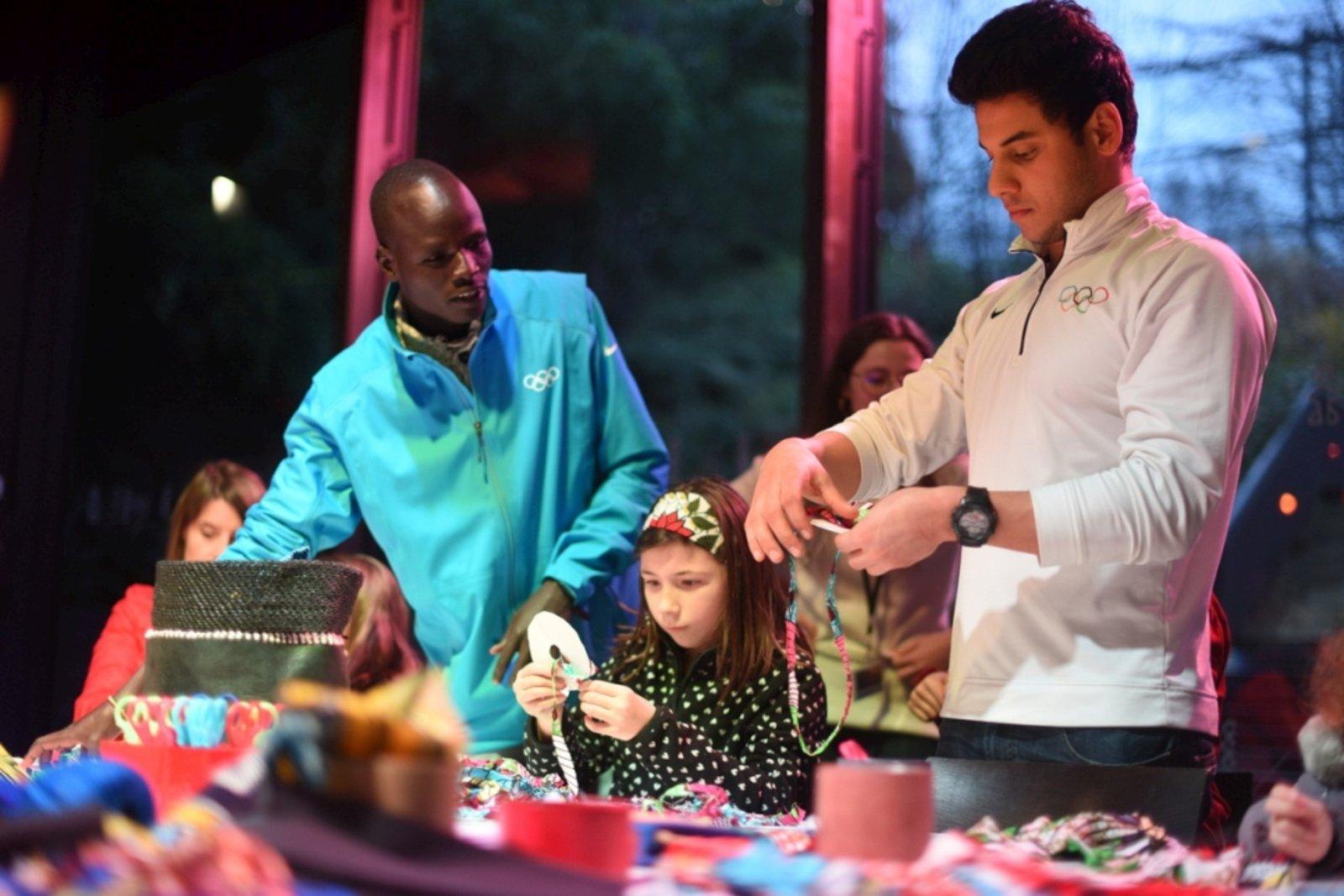 Niños franceses y  atletas refugiados dan regalos a menores que han huido de su país