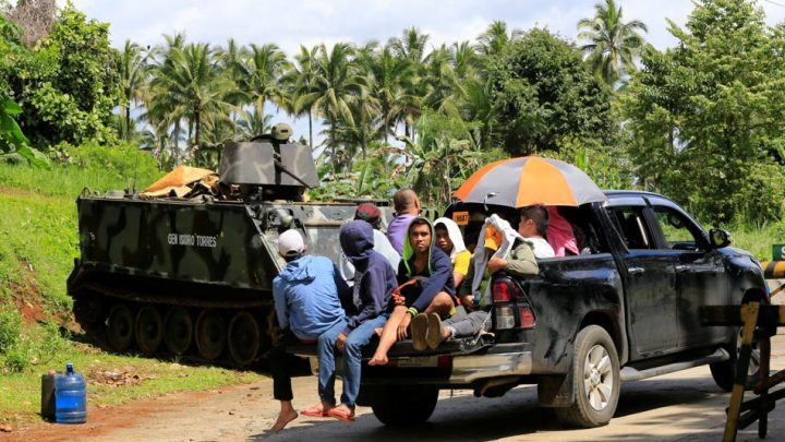 Evacuees drives past a government troop board on a armoured personnel carrier posted along a main highway of Pantar town, Lanao Del Norte, after residents starts to evacuate their hometown of Marawi city, southern Philippines May 24, 2017. REUTERS/Romeo Ranoco