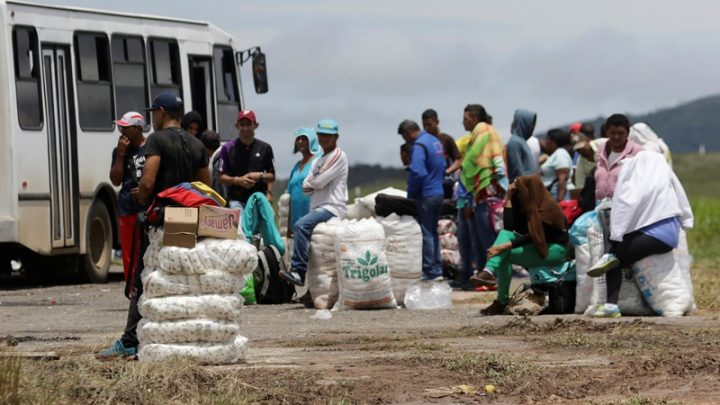 People stand next to packs of staple items and food while they wait for transportation in Santa Elena de Uairen, Venezuela August 3, 2016. Picture taken August 3, 2016.    REUTERS/William Urdaneta FOR EDITORIAL USE ONLY. NO RESALES. NO ARCHIVES.
